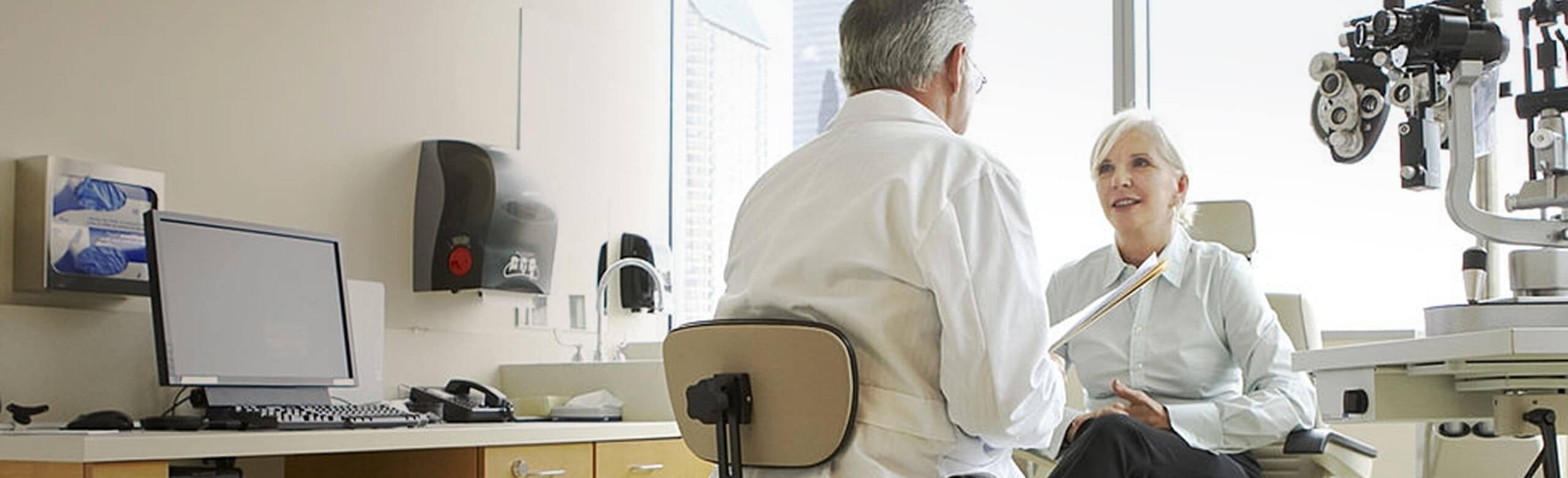 Eye doctor and patient speaking in exam room