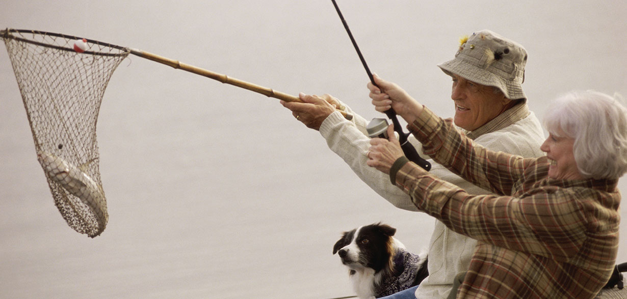 Elderly couple fishing with a net and fishing rod